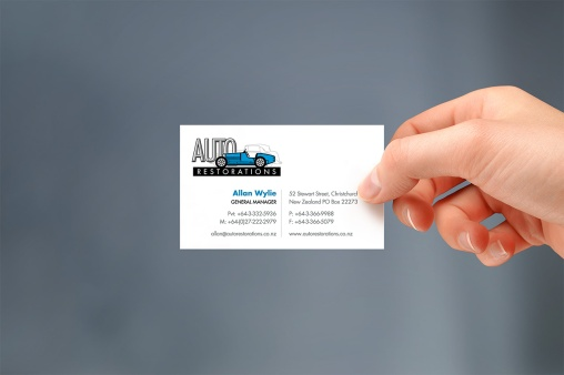 Auto Restorations business card, hand held.