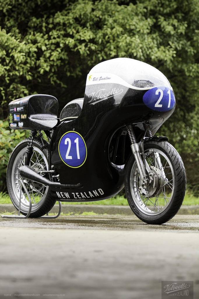 Eldee Velocette classic racing motorcycle, starboard front three-quarter view, carbon-fibre fairing, fairing, sponsors logos on seat, publicity photo, photography, product design, handlettering