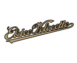 Eldee Velocette, hand-built classic racing motorcycle logo and automotive product badge. 'Coca-Cola' style sloped and looped copperplate lettering in gold outlined in black on a white background. Client: Velocette Racing New Zealand. Disciplines: Brand and identity systems design, Handlettering.