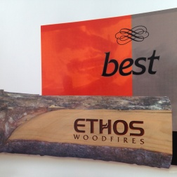 Ethos Woodfires 'warm your world' point of sale retail display collateral. A custom cut log laser etched with the Ethos brand acts as a display rack for the Ethos 'best' product catalogues on the shop floor.