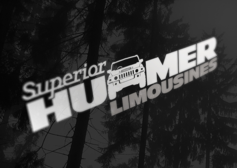 Close up of the Superior Hummer Limousines brand, detail view of decal on gloss black vehicle paintwork.