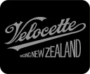 Velocette Racing New Zealand organisation logo. Classic racing motorcycle enthusiasts organisation brand. 'Coca-Cola' style sloped and looped copperplate lettering in metallic gold on a black background, consistent with the historic livery of Velocette motorcycles. Brands for New Zealand / International organisations.