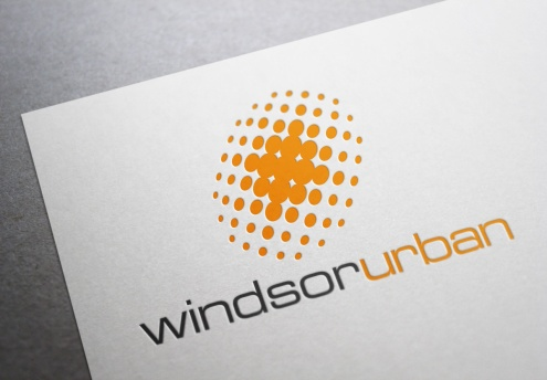 Windsor Urban symbol and type logo and trademark, two colours bright orange and dark grey on white. The symbol is a stylized pool of light drawn in coarse halftone dots that form a radial glow from the centre out within an implied slanted oval shape. Windsor Urban name is set as a unit, in clean extended sans-serif Eurostile font, the words differentiated by a colour change from dark grey to orange. Company rename and rebrand. Brands for New Zealand companies, Christchurch New Zealand.