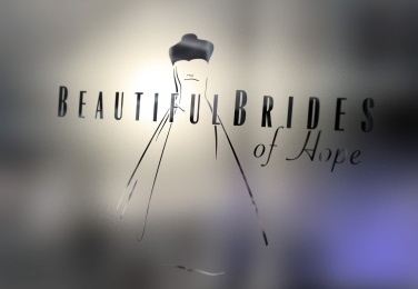 Closeup of Beautiful Brides of Hope bridal couture logo on frosted window glass. The finessed bridal illustration and type together create an elegant integrated singular brand expression. Graphic design, logo design, Christchurch, New Zealand.