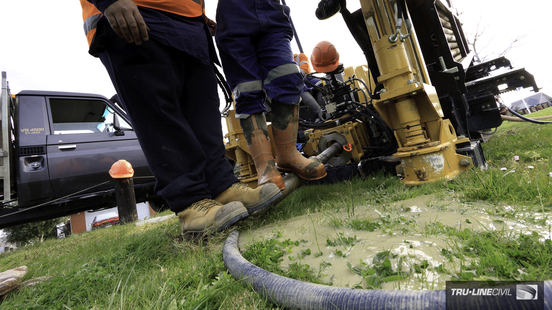 The weight of two men on the entry drill rod helps the pilot bit achieve bite into the sandy ground. Horizontal Directional Drilling, Tru-Line Civil, documentary photography, Parklands West, Christchurch, New Zealand, Gravity Wastewater Replacement, HDD