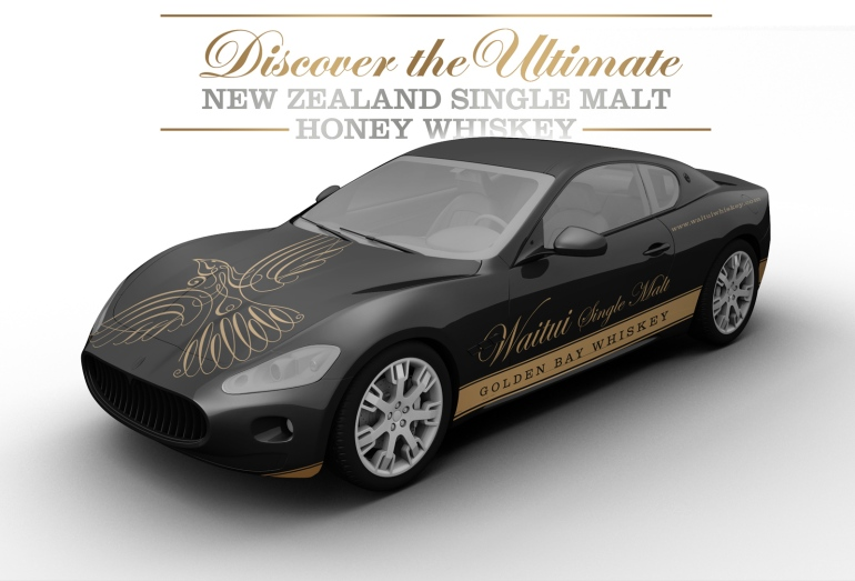 "Perspective view of ""Waitui Single Malt Golden Bay Whiskey"" attractively branded promotional black and gold sports car along with one of Waitui's distinct message pillars ""Discover the Ultimate New Zealand Single Malt Honey Whiskey"". The promotional vehicle is intended to build excitement and anticapation around the launch event and beyond."