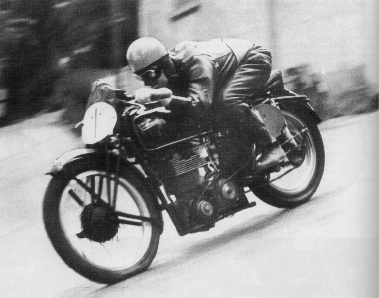 The defining image from Velocette's heyday on the international racing circuit pre-war. Stanley Woods flying down Bray Hill on his way to victory in 1939 Junior Manx race. Note the 'Huntley & Palmer' head, a wry comment on the biscuit tin size & shape of the casting—a nickname coined by Harold Willis. Willis was director, engineer and race chief of Veloce Ltd., makers of the Velocette motorcycle, until his untimely death on the eve of this race in June 1939.