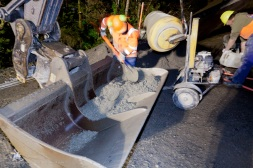 The concrete mix is delivered to the top of the culvert in an excavator bucket.