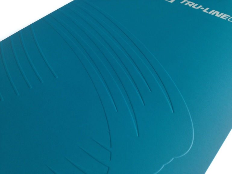 Detail of the cover of Tru-Line Civil presentation folder with a focus on the up-scale blind emboss of the logo the core of the corporate identity system. Craftsmanship is attention to detail.