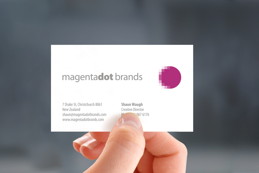 Front of MagentaDot Brands business card, hand held.