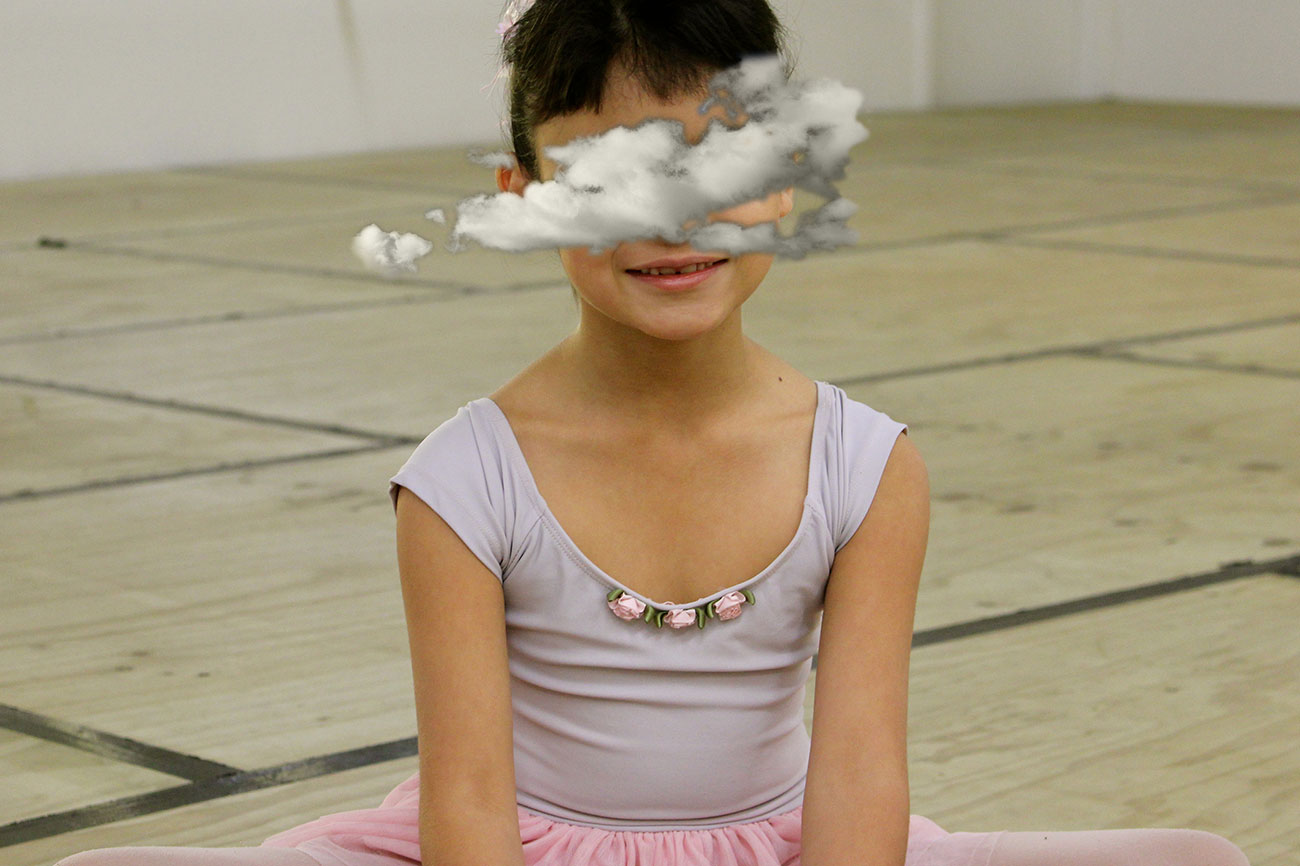 Young ballet dancer seated on studio floor.