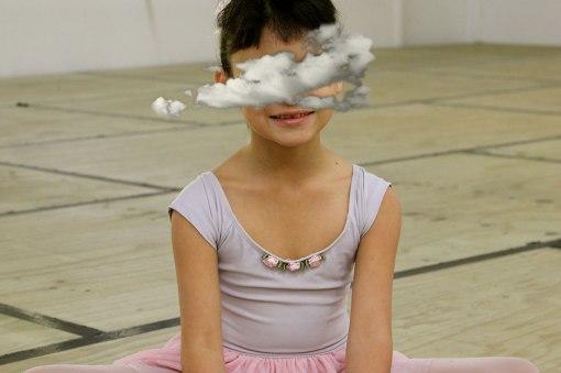 Young ballet dancer seated on studio floor.