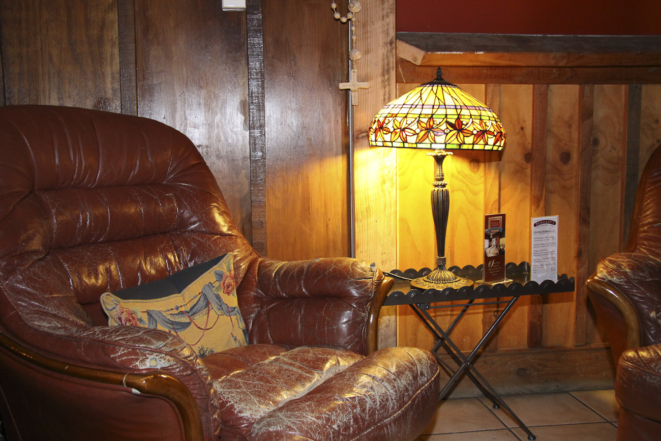 Pomeroy's Old Brewery Inn English style pub interior details. Art Deco lamp, wood panelling and comfy leather armchair.