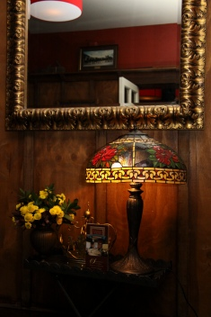 Pomeroy's Old Brewery Inn English style pub interior details. Art Deco lamp, gilded mirror and fresh cut flower arrangement.