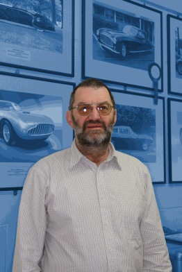 Concours award winners form the background of this informal portrait of Allan Wylie, managing director, reception area, Auto Restorations.