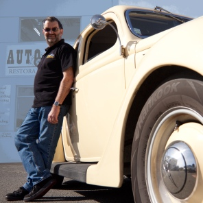 Auto Restorations skilled workforce informal portrait of Allan Wylie, managing director, leaning against his 1938 Ford roadster.
