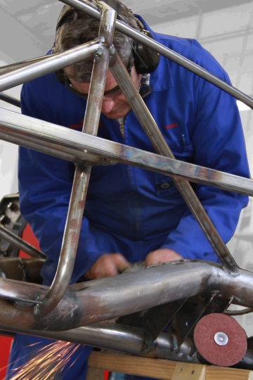 "Andy Wylie hand finishing the welding on the bespoke space frame of a 1953 Barchetta recreation ""kit"" car, in the Custom Coachwork Shop at Auto Restorations."