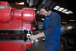 Aaron Dunlop forming a custom panel on the English wheel, Panel Shop, Auto Restorations.