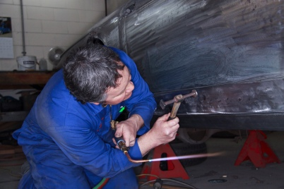 Bob Sterling precision fitting new bespoke aluminium panels on a classic Ferrari restoration in the Panel Shop at Auto Restorations.