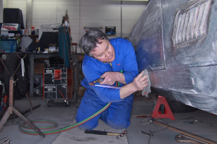 Bob Sterling precision fitting new bespoke aluminium panels on a classic Ferrari restoration in the Panel Shop at Auto Restorations.