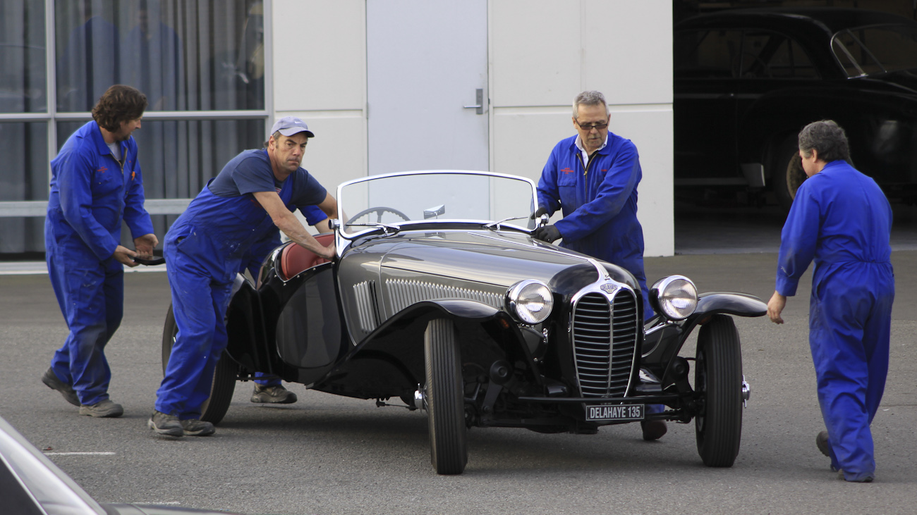 Four of Auto Restorations skilled workforce wheel a custom body Delage Roadster into position in the carpark.