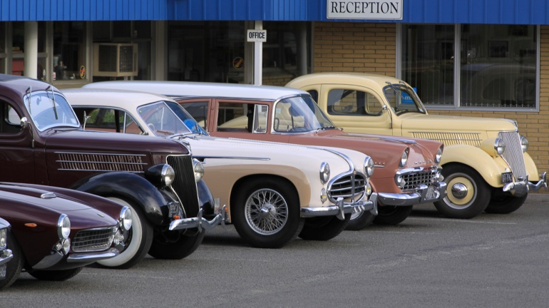 Lineup of classic cars in carpark of Auto Restorations, Stewart Street Christchurch workshop.