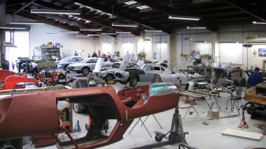 Wide view of in-progress restorations of rare classics in the Panel Shop and at Auto Restorations. Includes a Siata 280CS Balbo, an Alfa Romeo, a Fiat, a pair of Ferrari in the background and a Ferrari Lusso suspended upside down in the cradle in the foreground.