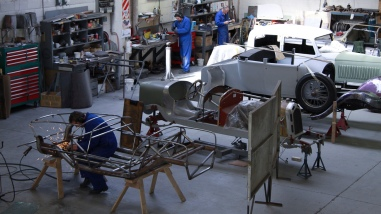 "In the foreground Andy Wylie is hand finishing the welding on the bespoke space frame of a 1953 Barchetta recreation ""kit"" car, in the Custom Coachwork Shop at Auto Restorations."