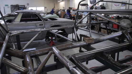 "In the foreground the bespoke space frame of a 1953 Barchetta recreation ""kit"" car, in the Custom Coachwork Shop at Auto Restorations."
