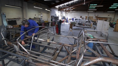 "Andy Wylie proofing against the plans the as-built bespoke space frame of a 1953 Barchetta recreation ""kit"" car, in the Custom Coachwork Shop at Auto Restorations."