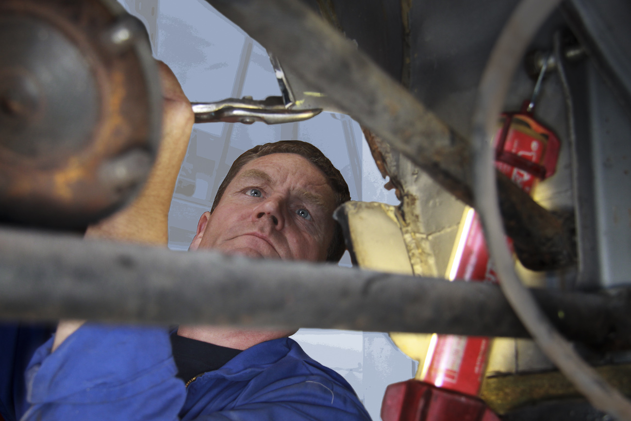 Glenn Birnie at work on a classic car up on the hoist in the Mechanical Shop at Auto Restorations.