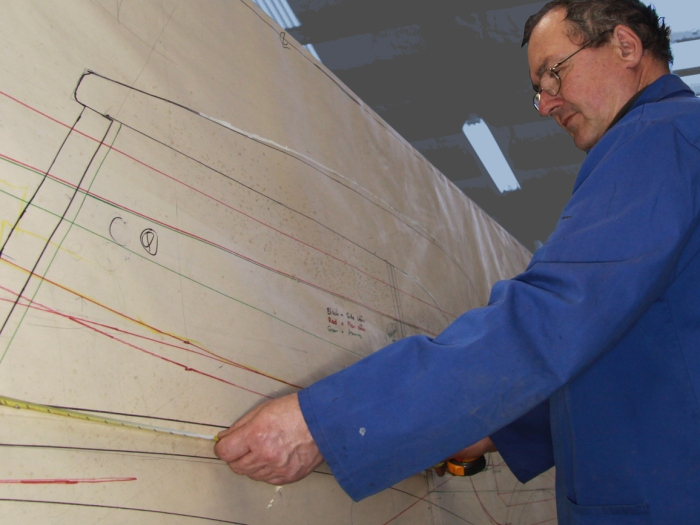 Graeme Climo dimensioning a bespoke aluminium body panel for a classic Delage restoration in the Custom Coachbuilding Shop at Auto Restorations.