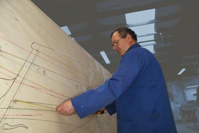 Graeme Climo dimensioning a bespoke aluminium body panel for a classic Delage restoration in the Custom Coachbuilding Shop at Auto Restorations.