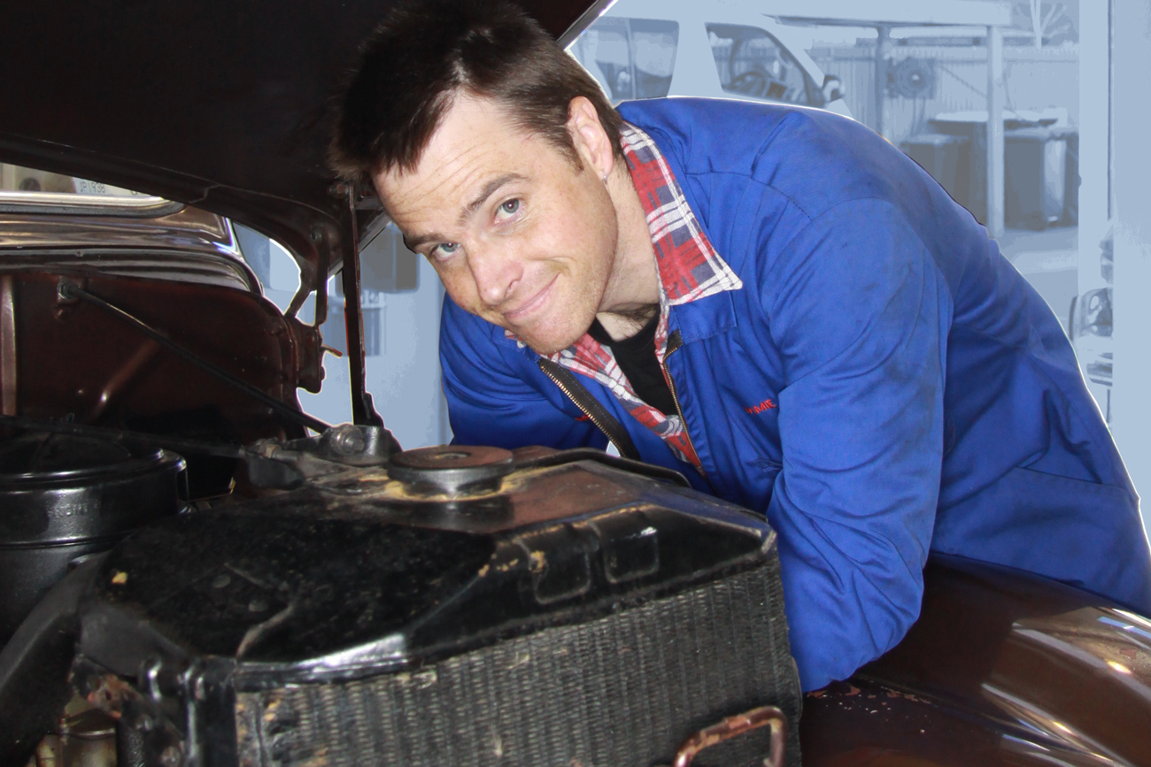 Jamie Graham making auto electrical repairs under the bonnet of a 1930s classic American V8 in the Machine Shop at Auto Restorations.