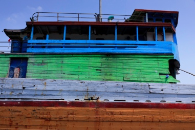 The colourful hull and bridge of a lambo or lamba type of motorised Pinisi at Sunda Kelapa, old harbour of Batavia, now Jakarta.