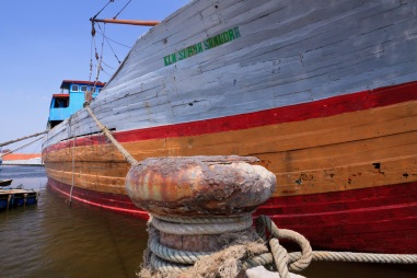 The colourful hull of a lambo or lamba type of motorised Pinisi, named KLM SURYA SANUDRA, moored at the port of Sunda Kelapa, Jakarta, Indonesia.