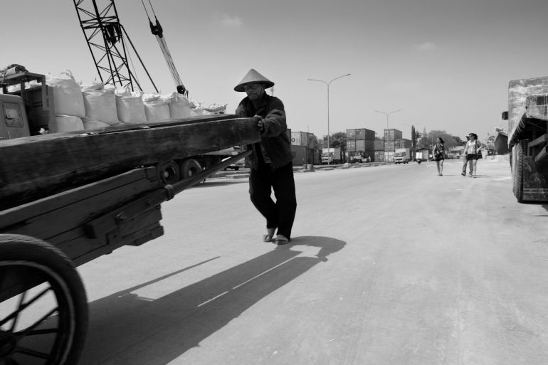 Coolie transports sawn teak logs on a hand pushed cart in heat of the mid-day sun (historical term for manual labourers from Asia), at the port of Sunda Kelapa, Jakarta, Indonesia