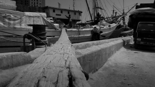 Traditional old wooden gangplank leads from the wharf at Sunda Kelapa, old harbour of Jakarta, to the deck of a Lamba type of motorised Pinisi.