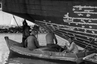 The stern of a motorised Pinisi is being sanded, scraped back and cracks filled with epoxy above the waterline by 5 coolies working off two dinghis. Sunda Kelapa, old harbour, Jakarta, Indonesia.