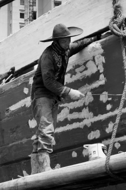 The midships of a motorised Pinisi being repainted with roller and brush applied lacquer above the waterline by a coolie working off a suspended plank.