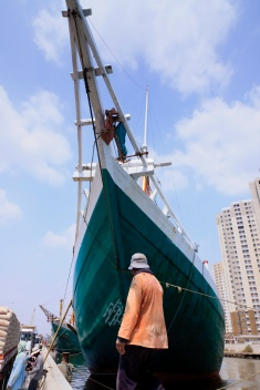 A coolie walks in front of the prow of a magnificent Pinisi traditional Indonesian boat. Port of Sunda Kelapa, old harbour, Jakarta.