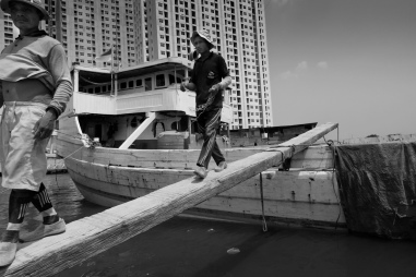Two coolies walk the gangplank between the deck of a Pinisi and the wharf in the old port of Sunda Kelapa, Jakarta.
