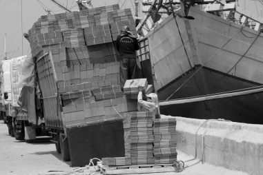 A coolie hand loads flat-packed cardboard boxes onto a wooden pallet on the wharf prior to loading into an awaiting Pinisi freighter using a deck crane.