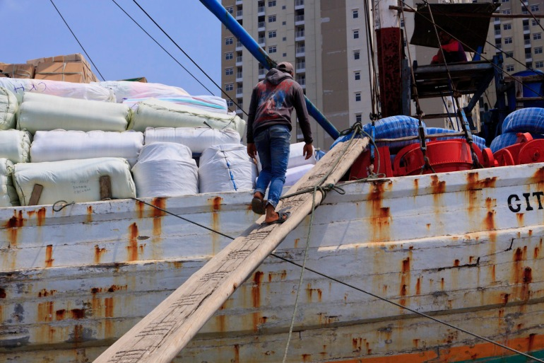 Coolie walks up the gangplank to board a Pinisi at the port of Sunda Kelapa, Jakarta, Indonesia.