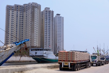 Freight trucks lined up on the wharf alongside motorised Pinisi at the old port of Sunda Kelapa, are towered over by apartment buildings.