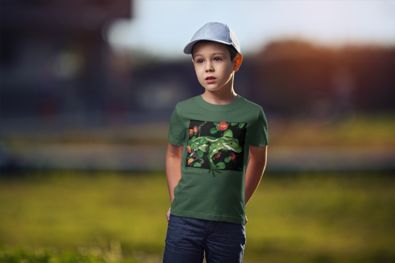 A boy standing in a forest green jewelled gecko New Zealand t-shirt against a blurry background.