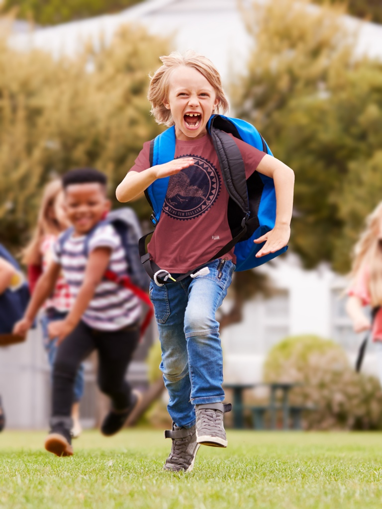 A cheerful young boy running towards the camera in a dark red kiwi New Zealand t-shirt.