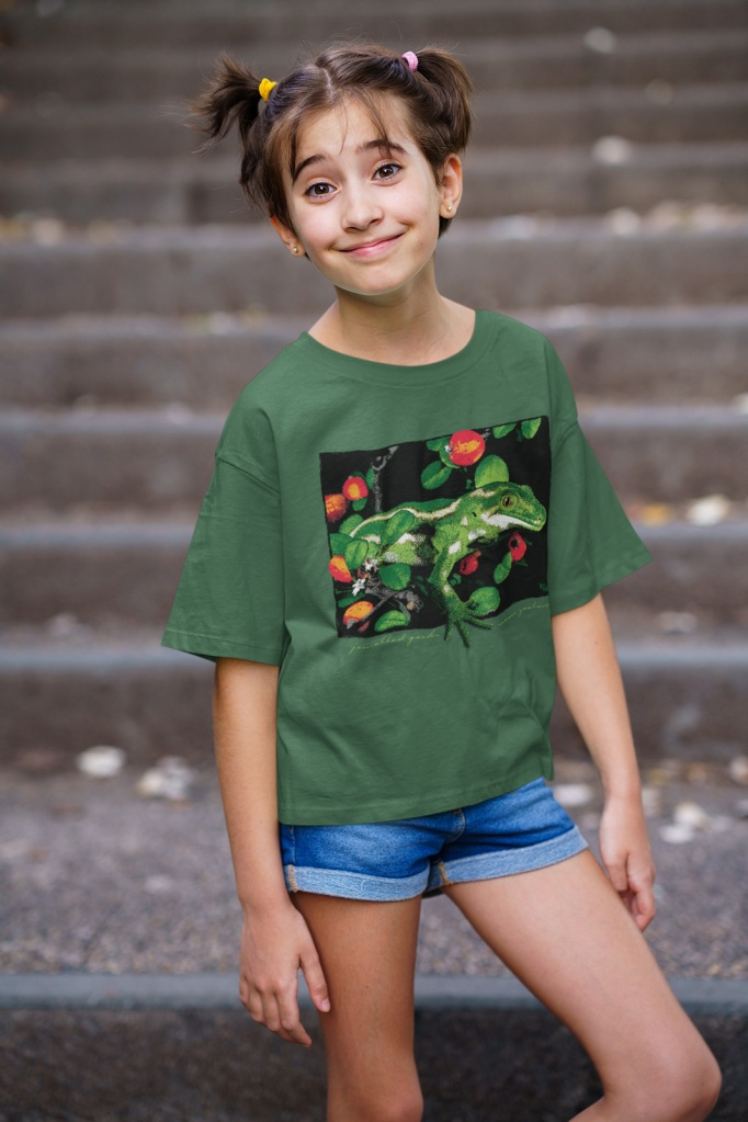 A young girl in a forest green jewelled gecko teeshirt posing in front of concrete stairs.
