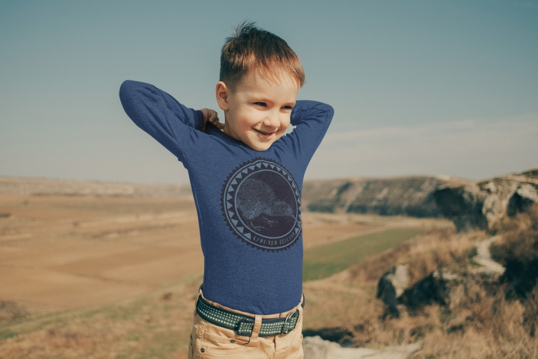 A kid wearing a dark blue long sleeve kiwi t-shirt standing in an alpine meadow.