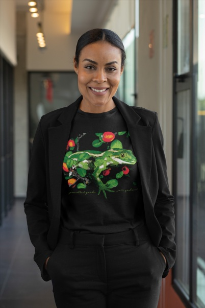 A professional woman posing in a black jewelled gecko t-shirt at the office.